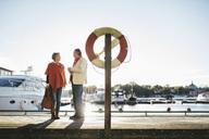 Full length of senior couple standing on pier against sky - MASF03647