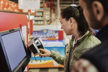 Female customer doing payment while standing with man at grocery store - MASF03668