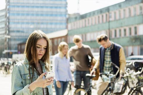 Young woman using smart phone at university campus - MASF03671