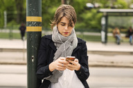 Young woman using mobile phone while listening to music through headphones at tram station - MASF03677