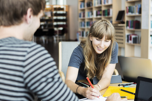 Young woman with male friend studying together in university library - MASF03680