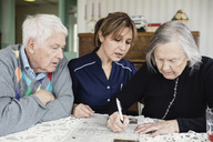 Caretaker assisting senior woman in solving crossword puzzle at nursing home - MASF03692