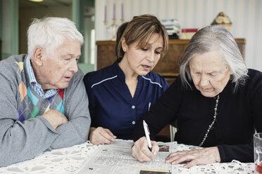 Caretaker assisting senior woman in solving crossword puzzle at nursing home - MASF03692
