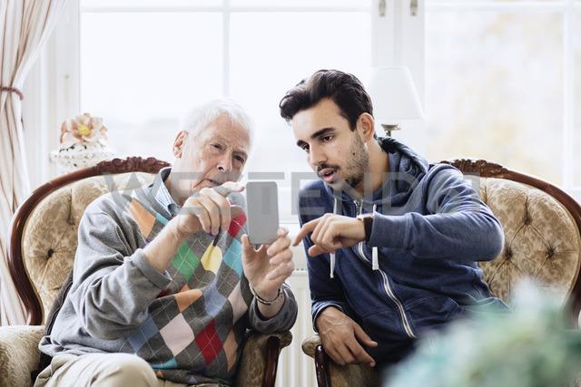 Caretaker assisting elderly man in using mobile phone at nursing home - MASF03695