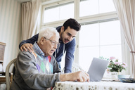 Caretaker and senior man using laptop in nursing home - MASF03698