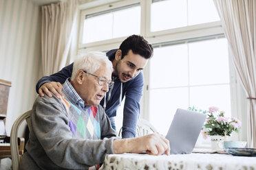 Caretaker and senior man using laptop in nursing home - MASF03698