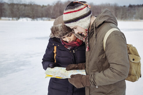 Couple looking at map while standing on field during winter - MASF03704