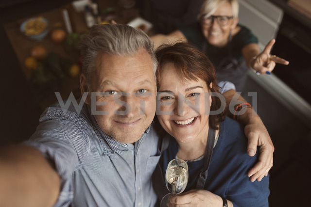 Cheerful mature man with arm around woman while taking selfie in kitchen - MASF03731