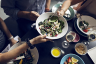 Cropped image of friends holding salad bowl at table - MASF03734