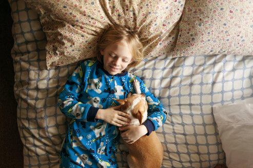 Overhead shot of smiling boy sleeping with dog on bed - CAVF38021