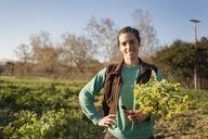 Portrait of happy woman holding flowers in field - CAVF38027