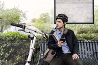 Young male commuter holding smart phone while sitting at bus stop - CAVF38036