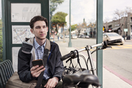Thoughtful male commuter holding smart phone while sitting at bus stop - CAVF38039