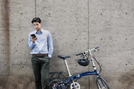 Businessman using smart phone while standing by bicycle against wall - CAVF38042