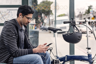 Male commuter using smart phone while sitting with bicycle at bus stop - CAVF38048