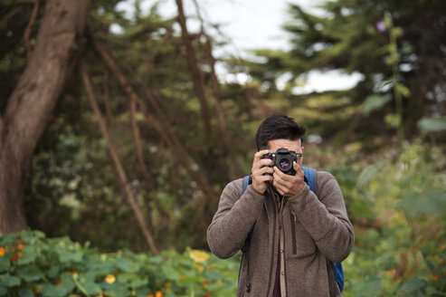 Male hiker photographing in forest - CAVF38099