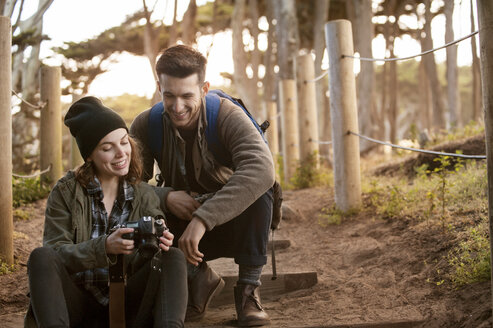 Hiking couple watching photographs on camera at forest - CAVF38108