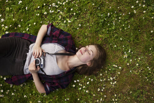 Overhead view of woman holding camera while relaxing on grass at park - CAVF38117