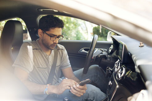 Man using mobile phone while sitting in car - CAVF38195