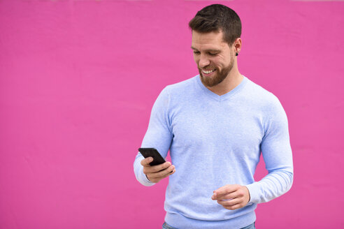 Smiling young man looking at his smartphone, pink background - JSMF00143