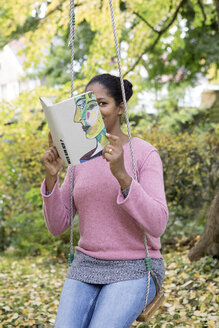 Woman covering face with book, reading poetry in a garden - PSTF00097