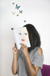 Woman covering face with book, reading poetry with butterflies - PSTF00100