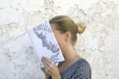 Woman covering face with book, reading poetry in front of wall - PSTF00103