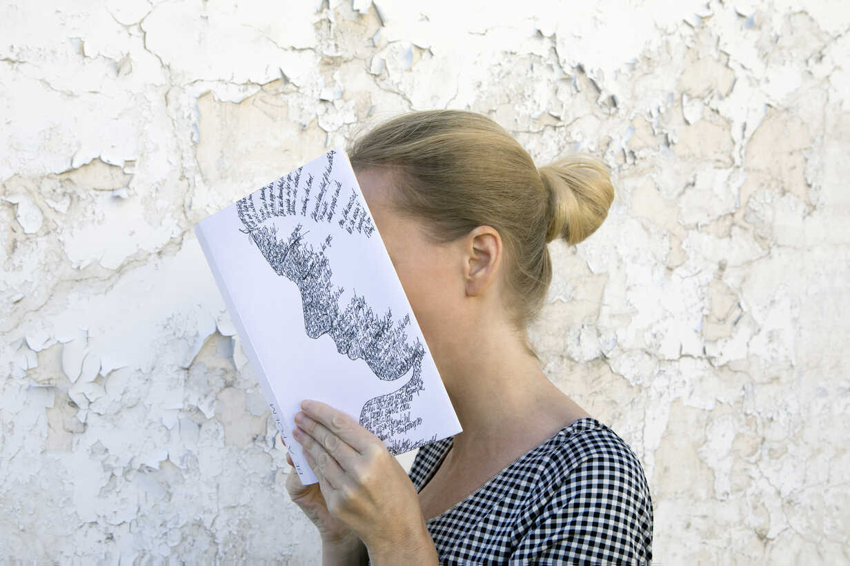 Woman covering face with book, reading poetry in front of wall - PSTF00103 - Petra Stockhausen/Westend61