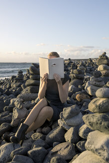 Woman covering face with book, reading poetry, eye looking through cover - PSTF00109