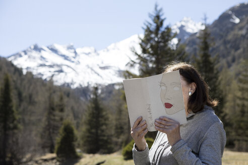 Woman covering face with book, reading poetry in the mountains - PSTF00112