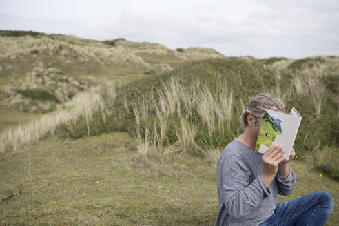 Man reading story book in the dunes, covering his face - PSTF00118