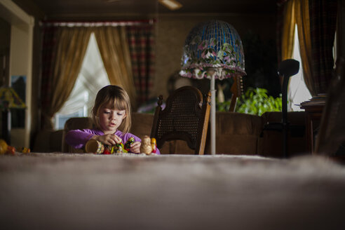 Girl playing with toys at dining table - CAVF38292