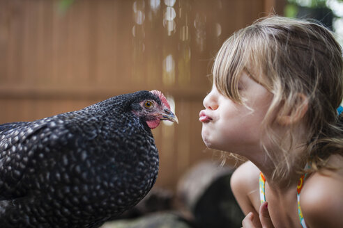 Happy girl puckering hen outdoors - CAVF38307
