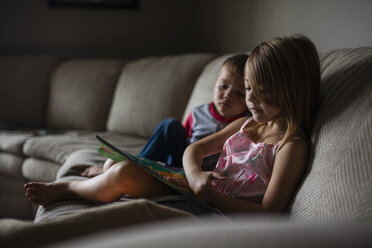 Siblings looking at picture book on sofa - CAVF38319