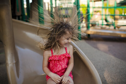 Happy girl playing flicking hair while sitting on slide - CAVF38331