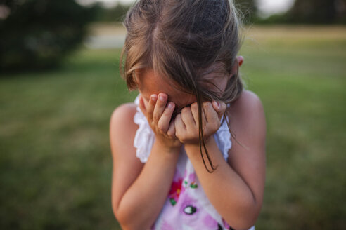 Close-up of girl covering face while crying outdoors - CAVF38355