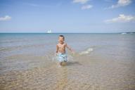 Cheerful boy running in sea against sky on sunny day - CAVF38361