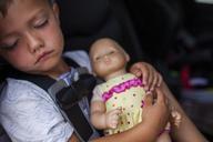 Boy sleeping with doll in car - CAVF38364