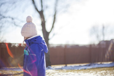 Side view of girl wearing knit hat standing in yard on sunny day during winter - CAVF38370