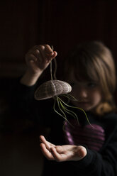 Girl playing with air plant hanging from sea urchin in darkroom - CAVF38376