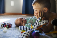 Baby girl looking at brother while lying on bed - CAVF38394