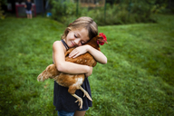 Smiling girl with eyes closed holding hen while standing in yard - CAVF38415