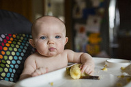 Portrait of cute shirtless baby girl with banana sitting on high chair - CAVF38442