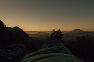 Czechia, Elbe Sandstone Mountains, Hiker lying in sleeping bag at sunrise - GUSF00625