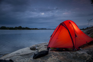 Tent on rock at lakeshore during dusk - MASF03753