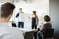 Young woman showing flipchart to friends and professor in classroom - MASF03768
