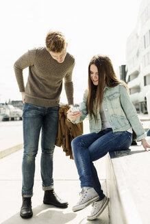 Woman showing smart phone to friend at campus - MASF03774