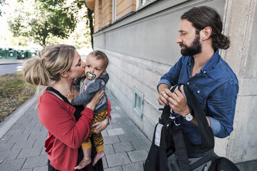 Working mother kissing baby boy while man holding carrier on sidewalk - MASF03822