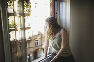 Young woman looking through window at home - MASF03828