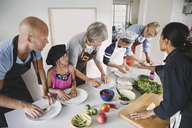 Woman guiding multi-generational family in preparing Asian food at kitchen - MASF03831
